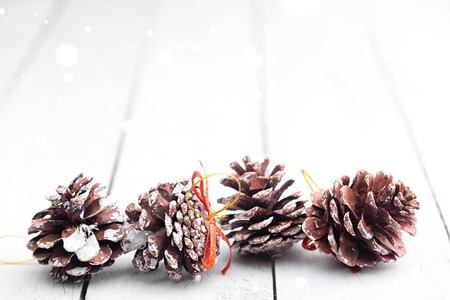 Fir cones in a row with sparkling flares and blurred background. Rustic christmas. White wooden table.