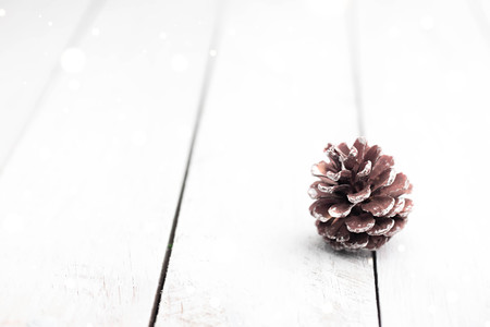 Single fir cone on white wooden table with sparkling flares and blurred background. Christmas decorations. 版權商用圖片