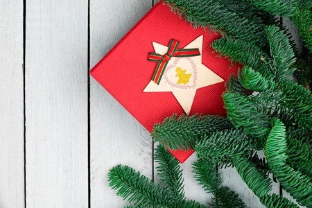 Christmas decorations on white wooden desk. Flat lay. Red gift box. Fresh christmas tree fir branches.
