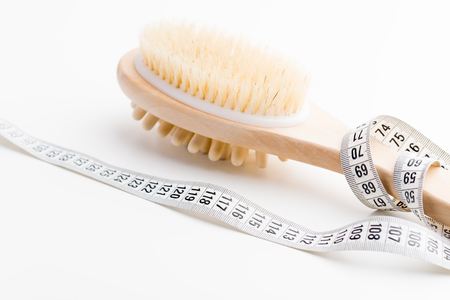 Dry massage brush with tape measure on white desk. Health and diet. Fitness concept.