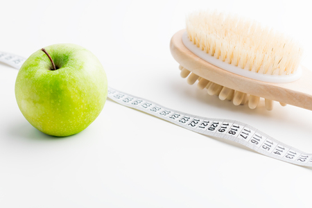 Dry massage brush with tape measure and single green apple on white desk.