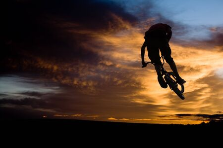 extreme: bmx rider against sky at sundown