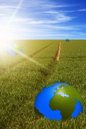 globalism: world globes in green field with a path and sunbeams