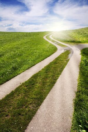 a curved path in the green field with a nice sky and sun in back Stock Photo - 7233076