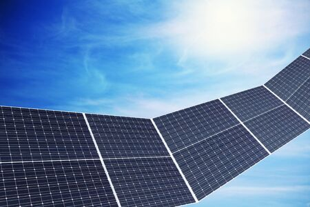 solar panels against cloudy sky with sun Stock Photo