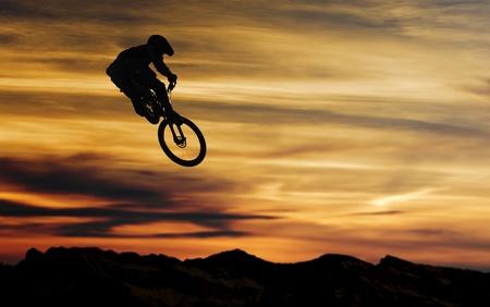 stunts: mountain bike salto contro la sundwon Archivio Fotografico