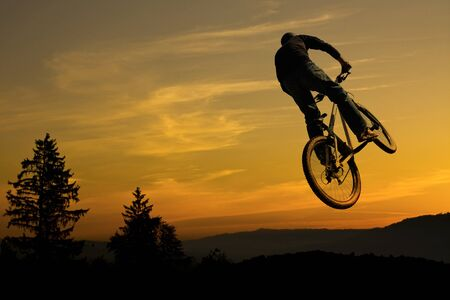 mountainbike: Mountainbike jump against sunrise sky with tree and mountain silhouettes in back