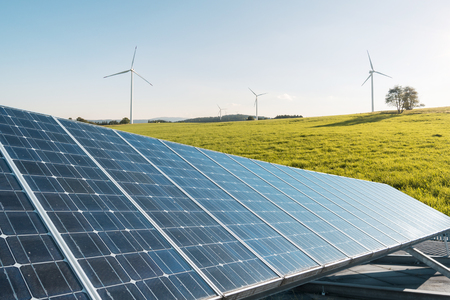 Wind mill and solar cell panel on a meadow for renewable energy production