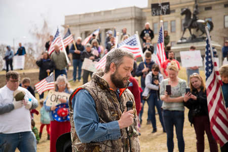 Helena, Montana - April 19, 2020: A man speaking and praying at a protest liberty rally at the Capitol again the shutdown due to Coronavirus. A crowd of protestors gathers holding American flags.