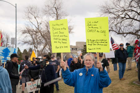 Helena, Montana - April 19, 2020: Senior citizen female protestor holding Bible scripture signs at a prayer rally at the state Capitol. Protesting the government shutdown and stay at home orders. Editorial