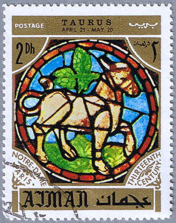 AJMAN - CIRCA 1971: A stamp printed in Ajman shows the horoscope sign of Taurus, series is devoted to the frescoes in the cathedral of Notre Dame, circa 1971 Stock Photo - 9000439