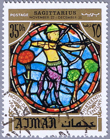 ajman: AJMAN - CIRCA 1971: A stamp printed in Ajman shows the horoscope sign of Sagittarius, series is devoted to the frescoes in the cathedral of Notre Dame, circa 1971 Stock Photo
