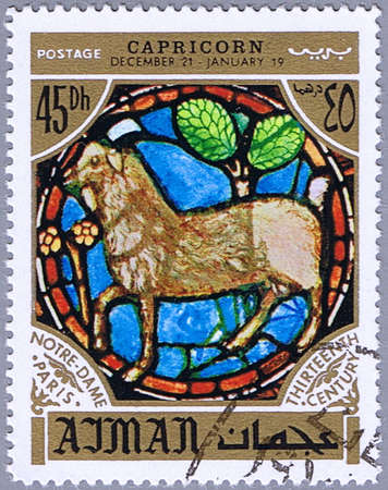 AJMAN - CIRCA 1971: A stamp printed in Ajman shows the horoscope sign of Capricorn, series is devoted to the frescoes in the cathedral of Notre Dame, circa 1971 photo