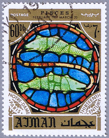 AJMAN - CIRCA 1971: A stamp printed in Ajman shows the horoscope sign of Pisces, series is devoted to the frescoes in the cathedral of Notre Dame, circa 1971 photo