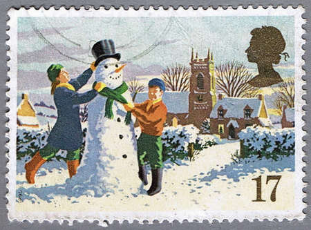 GREAT BRITAIN � CIRCA 1990: A stamp printed in Great Britain shows children are building a snowman, series is devoted to Christmas, circa 1990 photo