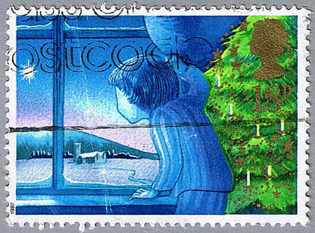 GREAT BRITAIN � CIRCA 1987: A stamp printed in Great Britain shows a boy looking out the window, series is devoted to Christmas, circa 1987 photo