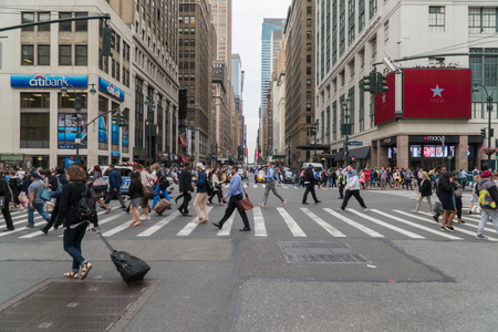 New York City, Circa 2017: Manhattan street intersection crosswalk wide angle long shot down avenue towards Times Square. Busy commuters walk to Penn Station Editorial