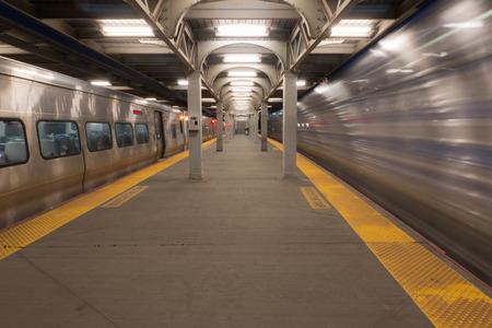 Long Exposure of high speed train passing station platform waiting departing train at railroad terminal hub Standard-Bild