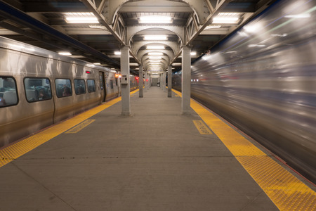 Long Exposure of high speed train passing station platform waiting departing train at railroad terminal hub Stock Photo