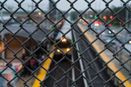 Passenger train arriving at station platform pick up passengers. Long Island people commute into New York City via railroad. Shallow depth of field through overpass fence.