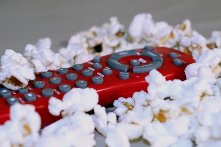 Delicious popcorn is scattered around a television remote control - a favorite movie time snack