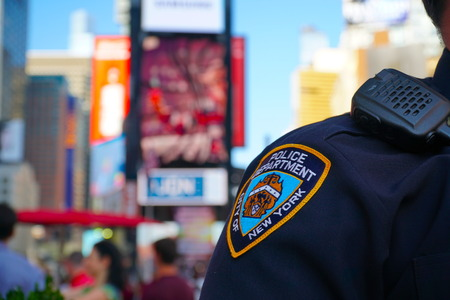 New York City - September 2016: NYPD sleeve patch shield on a police officer patrol Times Square Manhattan. Protect public from terror threats and ensure safety in central tourist landmark