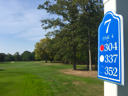 Public golf course hole number sign - Display distance to green from tee box markers for player to judge how far they will need to drive the ball down the fairway. Decision for type of club to use.