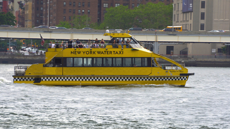 New York City - June 7 2016: New York City water taxi travels up the East River taking evening commuters from downtown Manhattan South Street Seaport by financial district to DUMBO area of Brooklyn Editorial