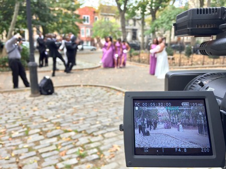 Behind the scenes of a videocamera taping a wedding party and beautiful bride and her family and friends before celebration reception. Event photography
