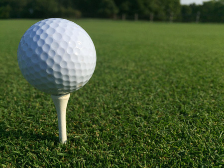 Low angle white golf ball sitting onto of tee for player to swing driver club and hit down fairway towards green and put into hole.