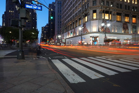 New York City - June 7, 2016: Long exposure night exterior shot in Herald Square outside Victoria Secret flagship Manhattan store. Light trails of car and taxi traffic driving uptown on 6th avenue.