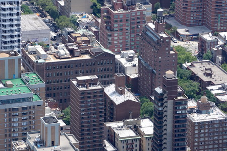 Aerial establishing photo of New York City buildings in the Manhattan skyline. Looking down on rooftops from high above.