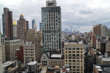 Aerial view establishing photo overlooking New York City apartment buildings towards downtown Manhattan on an overcast cloudy day.