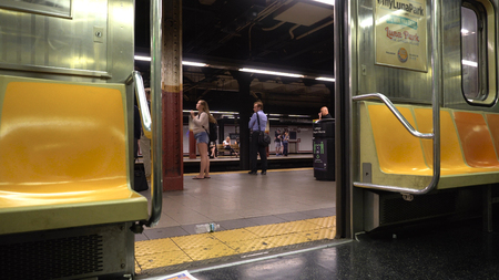 New York City - June 7 2016: POV photo sitting inside a New York City subway train looking out of the open door to tourists and commuters waiting on the platform during rush hour Фото со стока - 93826260