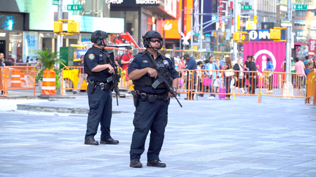 New York City - September 2016: NYPD Swat team officers armed with assault rifles patrol Times Square, heart of Manhattan and New York tourism. Target for terrorist attacks with suspicious package Editorial