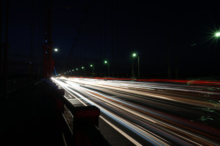 Light trail - busy commuter traffic driving over the George Washington Bridge between New Jersey and Manhattan New York City in the evening. Night time long exposure. Headllights and brake lights Stock Photo