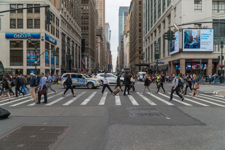 New York City, Circa 2017: 34th Street 7th Avenue crosswalk intersection in midtown Manhattan during a busy rush hour commute. People safety walk past traffic