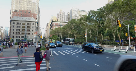 New York City, Circa 2017: Wide view outside NYC park of busy Manhattan intersection of cars passing and people walking across street in safety crosswalk on a summer day