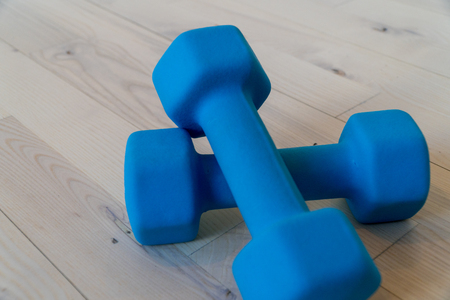 Blue dumbbell set of weights sit on a wood floor in a gym exercise studio space. Lifestyle fitness athletes use to shape and tone bodies into muscle mass. Stock Photo