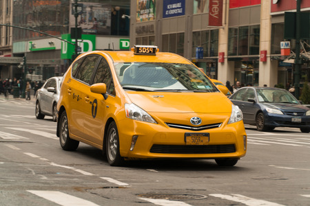 New York City - Circa 2017: Yellow taxi cab driving in streets of Manhattan on a busy day. Taking passengers to destinations around city. Hail cab or use mobile app to call Uber or Lyft.