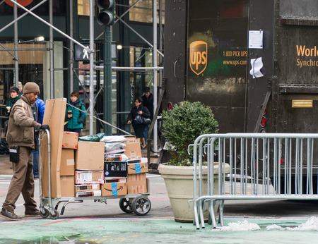 New York City - Circa 2017: UPS driver loading packages onto a cart from back of brown truck to deliver orders and boxes to customers in Manhattan. Sajtókép
