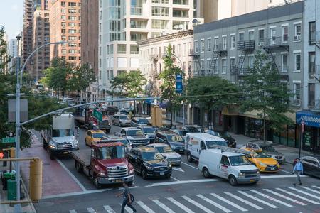 뉴욕시, 2017 년경 : 사람들이 횡단 보도를 안전하게 통과 할 때까지 기다리고 신호등 교차로에서 미드 타운 맨하탄 자동차. 낮 시간 외관 에디토리얼