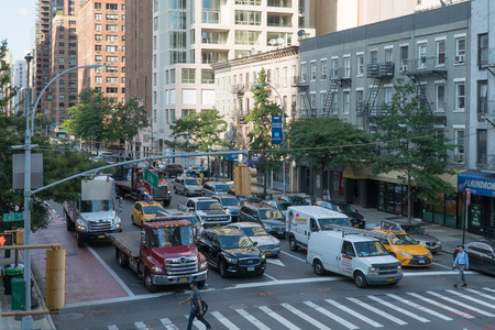 New York City, Circa 2017: Midtown Manhattan cars at traffic light intersection waiting for people to pass crosswalk safely. Day time exterior Redakční