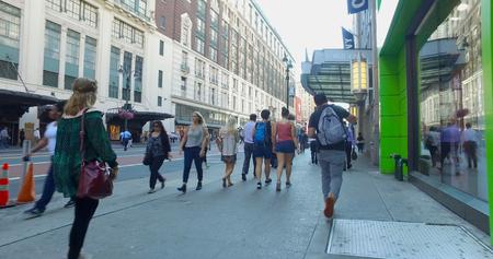 New York City, Circa 2017: POV view behind people walk down Manhattan sidewalk commute to work during morning rush hour.