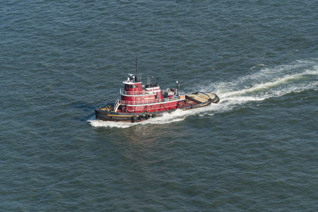 Aerial view of a New York City harbor tug boat sailing through water to assist large container and tank ships into port