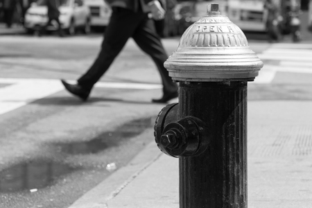 New York City fire hydrant on busy street corner intersection. Pedestrian people crosswalk in background. Black and white photo Banque d'images