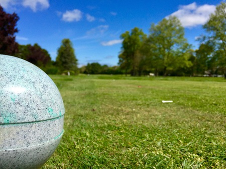Low angle view down the fairway looking past the tee box of a beautiful golf course on a warm summer day with clear blue skies. Golf outing wood tee sits on grass