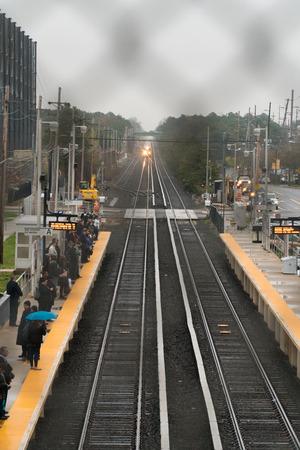 Long Island, NY - Circa 2017: Long Island Railroad train travel on track to station platform. People commute public transportation into Manhattan. Vertical Frame Editorial