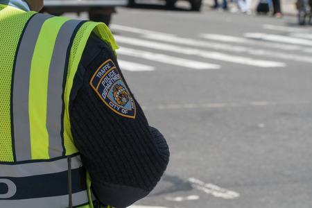 ニューヨーク市、サーカ2017:NYPD交通警察官は、朝のラッシュアワーの通勤中に交通を指示します。制服の袖にバッジパッチ