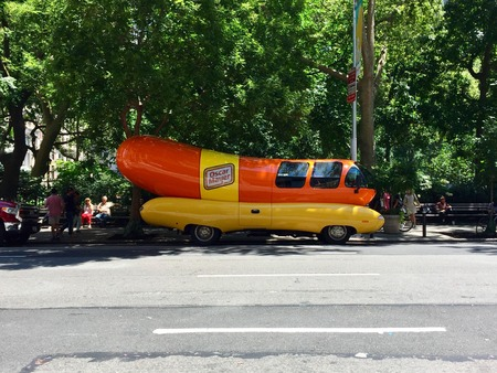New York City, Circa 2017: Oscar Mayer Wiener mobile outside Manhattan park on summer day. Promotional advertising vehicle shaped like hot dog